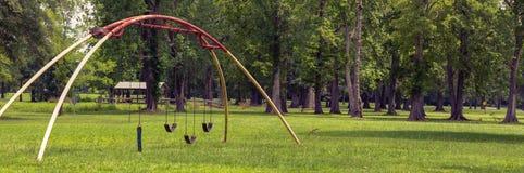 Łękowaty huśtawka set w disrepair w parku z piękną scenerią zdjęcie stock