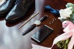Łęku krawat, buty, obrączki ślubne, telefon, zegar, panny młodej ` s bukiet obrazy stock