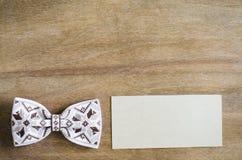 Łęku krawat i Opróżnia kartę na Drewnianym tle Zdjęcia Stock