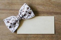 Łęku krawat i Opróżnia kartę na Drewnianym tle Obrazy Stock