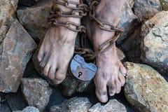 Łańcuchy z kędziorkiem na nogach niewolnik wśród kamieni Łańcuchy przy kostką Symbol niewolnictwo obrazy royalty free