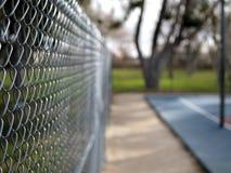 Łańcuszkowego połączenia ogrodzenie wokoło boisko do koszykówki w parku Fotografia Royalty Free