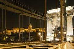 Łańcuszkowy most Budapest, Węgry zaświecał up przy nocą z parlamentu budynkiem Zdjęcie Stock