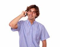 Łaciński mężczyzna ono uśmiecha się podczas gdy opowiadający na jego telefonie komórkowym Zdjęcia Royalty Free