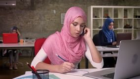 Ładna środkowa wschodnia kobieta jest ubranym różowego hijab opowiada nad jej smartphone pewnie i spokojnie, pisać przy miejsce p