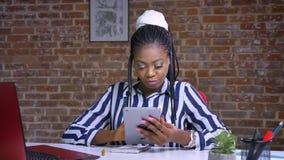 Ładna afrykańska dziewczyna pisać na maszynie na jej pastylce relaksuje i siedzi przy stołowym pobliskim czerwonym laptopem nad c