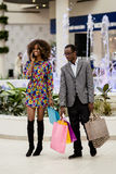 Ładna amerykanin para w zakupy centrum handlowym Kobieta opowiada na telefonu i mężczyzna przewożenia torbach Obrazy Stock