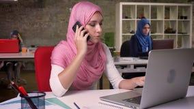 Ładna arabska kobieta w różowym hijab opowiada nad telefonu chłodem i relaksuje podczas gdy siedzący z zaufaniem w ceglanym biurz