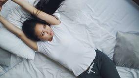 Ładna Azjatycka dama śpi na łóżku wtedy otwiera oczy rozciąga jej ręki z uśmiechem i Miękka poduszka i biała pościel zdjęcie wideo