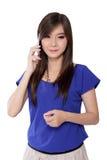 Ładna Azjatycka dziewczyna opowiada na telefonie komórkowym, odizolowywającym na bielu Obrazy Stock