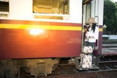 Ładna Azjatycka kobieta podróżnika pozycja i patrzeć pastylkę na pociągu Fotografia Royalty Free