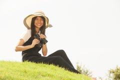 Ładna Azjatycka młoda kobieta szuka lornetki siedzi na kopu Zdjęcia Stock