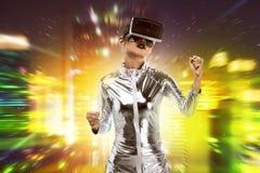Ładna azjatykcia kobieta jest ubranym srebnego lateksowego kombinezon i VR słuchawki Zdjęcia Royalty Free