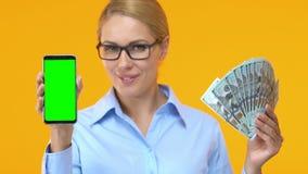 Ładna biznesowa kobieta pokazuje smartphone z zieleń ekranem i wiązką dolary zbiory wideo