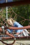 Ładna blond dziewczyna bawić się na arkanie czerwona sieć w lecie obraz stock