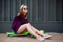 Ładna blond dziewczyna jest ubranym okulary przeciwsłonecznych, w kratkę koszula i drelichowych skróty, siedzi na jaskrawych logb zdjęcia royalty free