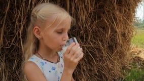 Ładna blond dziewczyna pije świeżego krowy mleko od szkła przeciw haystack w lecie na gospodarstwie rolnym zbiory