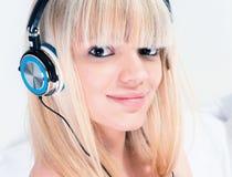 Ładna blond dziewczyna słucha muzyka na jej smartphone Obrazy Royalty Free