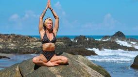 ładna blond dziewczyna w czerń wierzchołku relaksuje w joga pozy lotosie biega na skałach na purpury macie przeciw ocean fala zbiory wideo