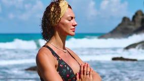 ładna blond dziewczyna w czerń wierzchołku relaksuje w joga pozy lotosie biega na skałach na purpury macie przeciw ocean fala zdjęcie wideo