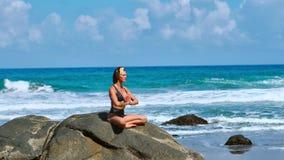 ładna blond dziewczyna w czerń wierzchołku relaksuje w joga pozy lotosie biega na skałach na purpury macie przeciw ocean fala zbiory