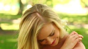 Ładna blondynka relaksuje w parku ono uśmiecha się przy kamerą podczas gdy wąchający kwiatu zbiory