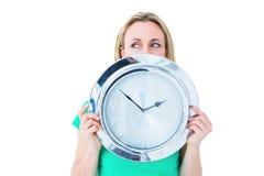 Ładna blondynka w przypadkowych ubraniach pokazuje zegar Obraz Royalty Free