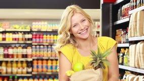 Ładna blondynka z papierową torbą robi aprobatom zbiory wideo