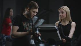 Ładna blondynki dziewczyna jest skrzętnym działaniem na ćwiczenie rowerze przychodzących wyjaśniać jej błąd w jej pracie na a chł zbiory