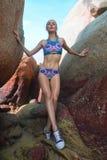 Ładna blondynki kobieta między skałami blisko morza podczas pięknego letniego dnia Zdjęcia Stock