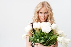 Ładna blondynki kobieta pozuje z bukietem kwiaty zdjęcie stock