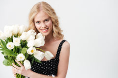 Ładna blondynki kobieta pozuje z bukietem kwiaty obrazy stock