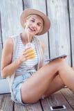 Ładna blondynki kobieta używa jej pastylkę i trzymający sok pomarańczowego Zdjęcie Stock