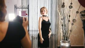 Ładna blondynki kobieta w koktajl sukni pozuje dla fotografa w ubraniowym butiku zdjęcie wideo