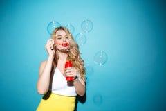 Ładna blondynki kobieta w lato odzieżowych podmuchowych mydlanych bąblach obraz royalty free