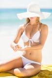 Ładna blondynki kobiety kładzenia suntan płukanka na jej ręce Zdjęcia Stock