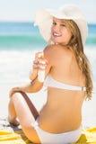 Ładna blondynki kobiety kładzenia suntan płukanka na jej ramieniu Zdjęcia Royalty Free