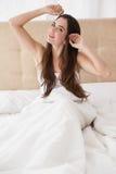 Ładna brunetka budzi się up w łóżku Obrazy Royalty Free