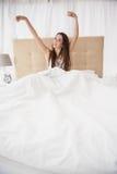 Ładna brunetka budzi się up w łóżku Fotografia Stock