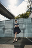 Ładna brunetka pozuje przeciw granit ścianie pod wiaduktem w słońc odbiciach Obrazy Stock
