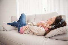 Ładna brunetka słucha muzyka na leżance Obrazy Stock