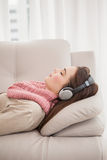 Ładna brunetka słucha muzyka na leżance Zdjęcia Stock