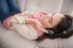 Ładna brunetka słucha muzyka na leżance Obraz Royalty Free