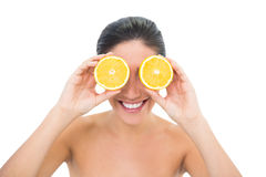 Ładna brunetka trzyma dwa pomarańczowej połówki nad jej oczami Fotografia Royalty Free