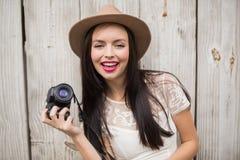 Ładna brunetka trzyma jej kamerę Obrazy Royalty Free