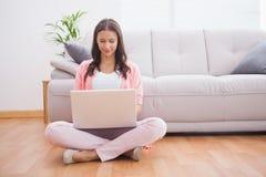 Ładna brunetka używać jej laptopu obsiadanie na podłoga Zdjęcia Stock