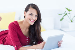 Ładna brunetka używać jej pastylka komputer osobistego kłama na jej łóżku Obrazy Royalty Free