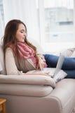 Ładna brunetka używać laptop na leżance Obrazy Royalty Free