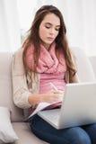 Ładna brunetka używać laptop na leżance Zdjęcie Royalty Free