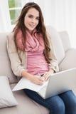 Ładna brunetka używać laptop na leżance Zdjęcia Royalty Free